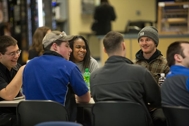 students sitting at table smile during Adam Grabowski show at moraine park