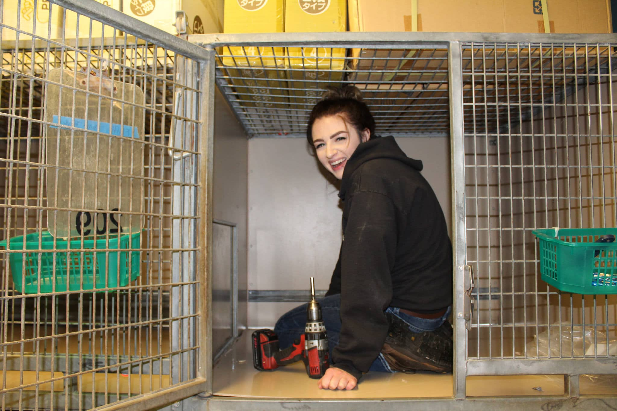 image of woman sitting in a kennel