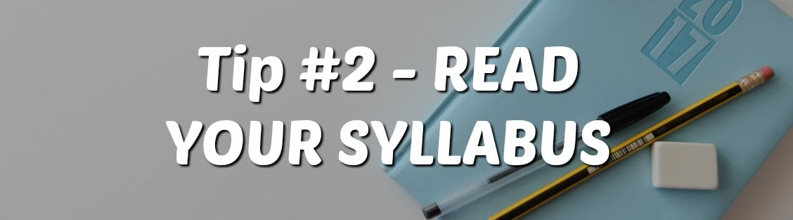 "Picture of a white desk with a 2017 planner, black pen, pencil, and eraser laying on top. Text overlay says, ""Tip #2- Read your syllabus."""