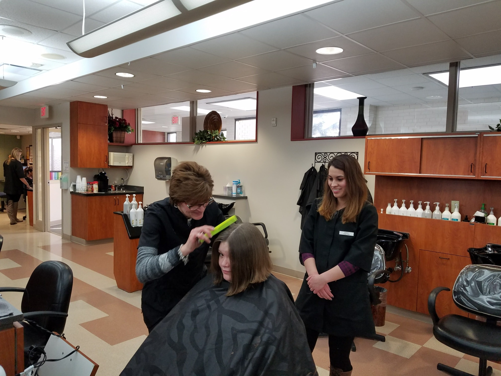 Cosmo student and instructor performing haircut on client