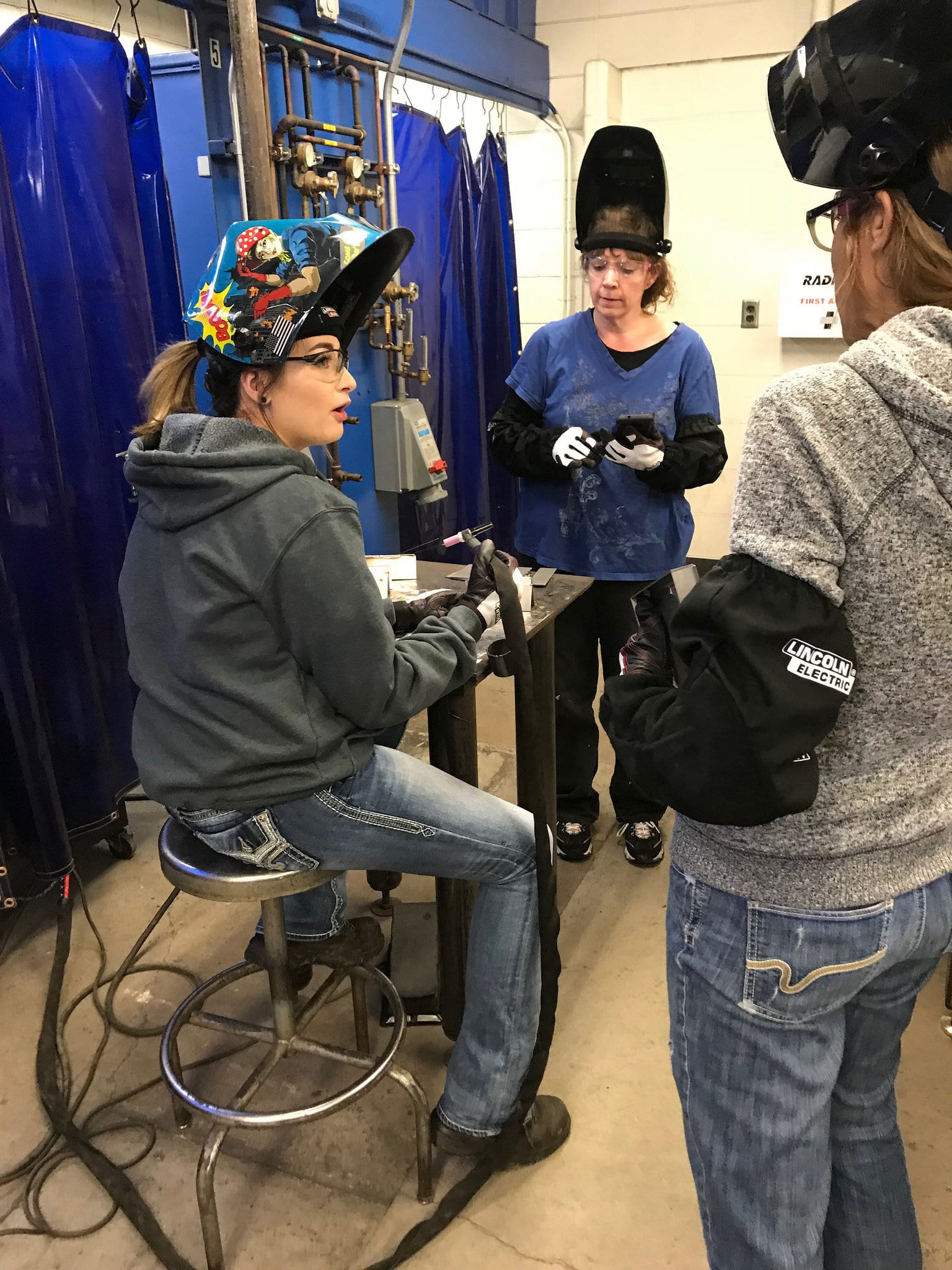 three females in welding lab with helmets on
