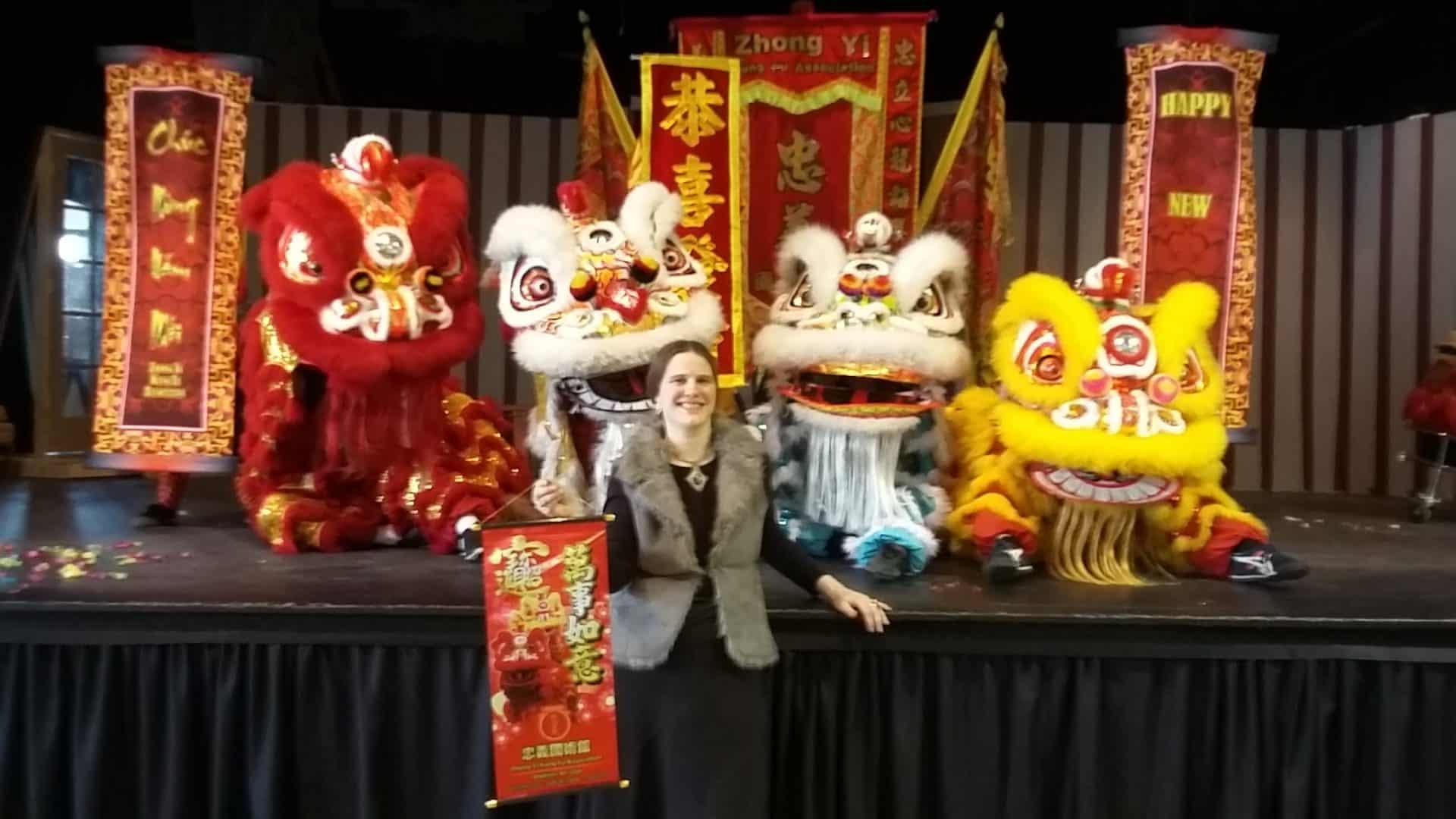 Anita stands near Zhong Yi Lion Dancers
