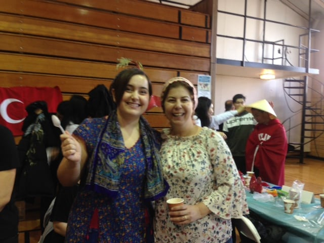 two woman smile together at global fair