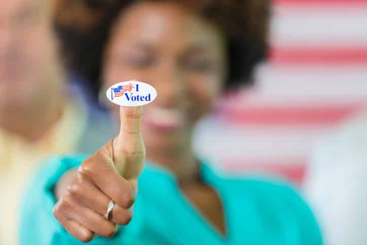 "Smiling african american woman with an ""I voted"" sticker on her thumb."