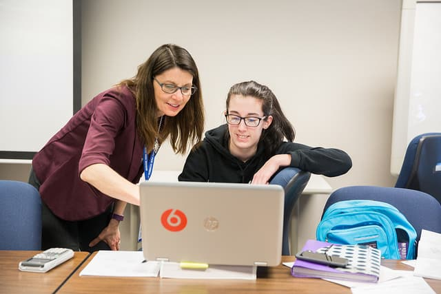 Accounting instructor teaching a female student on the computer.