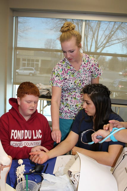 Young man being taught by Moraine Park medical assistant students on how to check for a pulse.