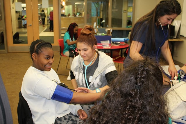 Moraine Park Medical Assistant student checking the blood pressure of a teenage girl.