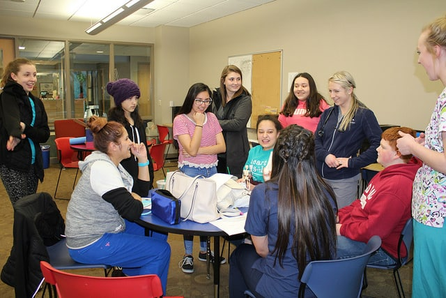 Moraine Park Medical Assistant students gathered around a table with the Fond du Lac Boys and Girls club.