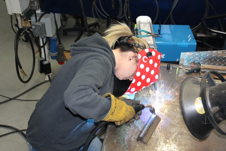 Female student practicing welding.