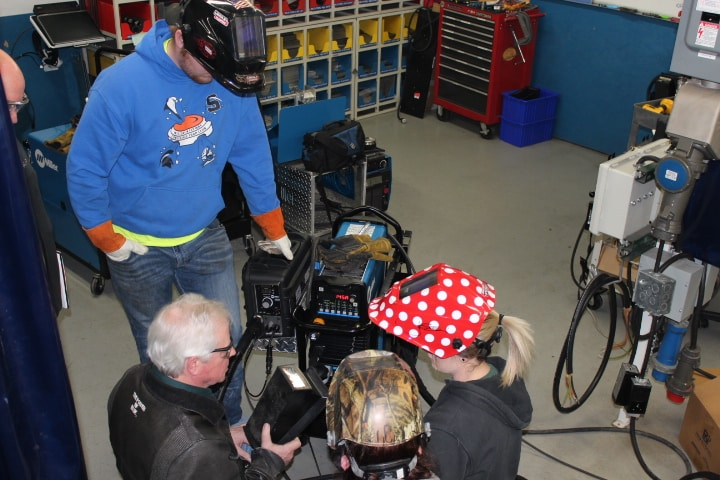 Welding students being shown how to use new welding technology.