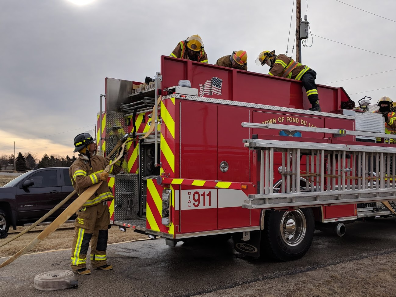 Student training to be firefighters unraveling the rope from the firetruck.