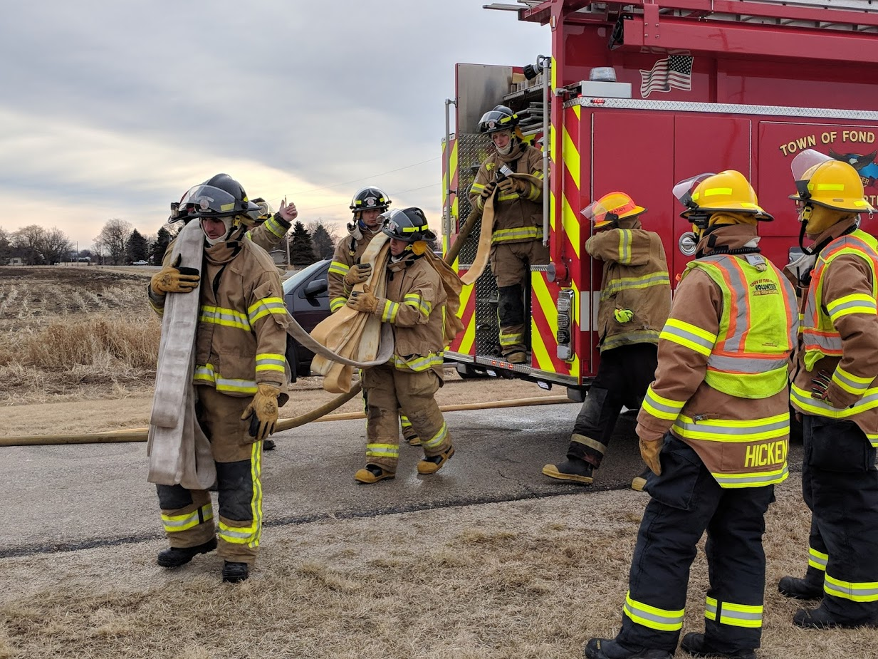 Firefighter students unraveling fire hose from the fire truck.