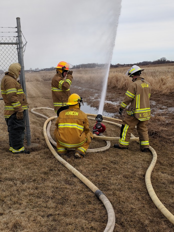 Firefighter students testing a fire hose.