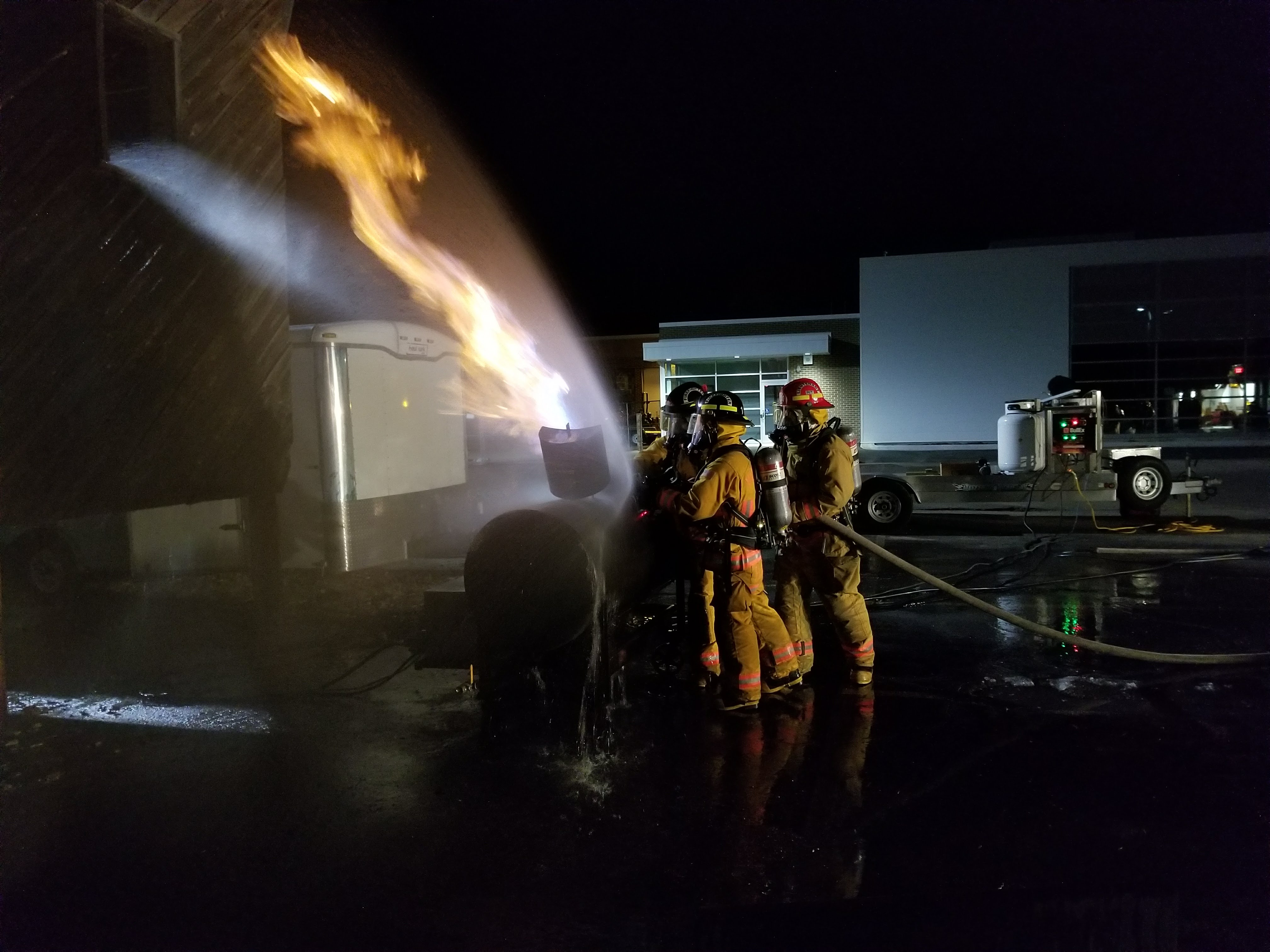 Firefighters worth together to extinguish a flame.