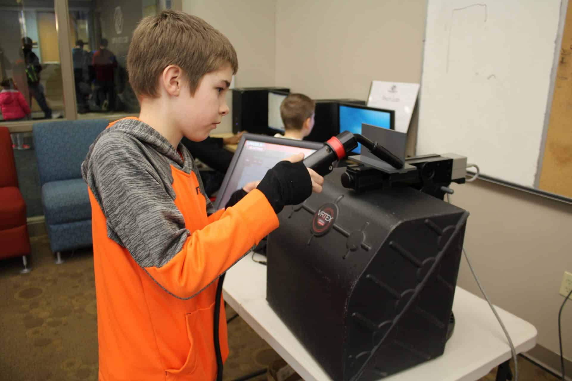 Young boy trys out a virtual welder at Boys and Girls Club