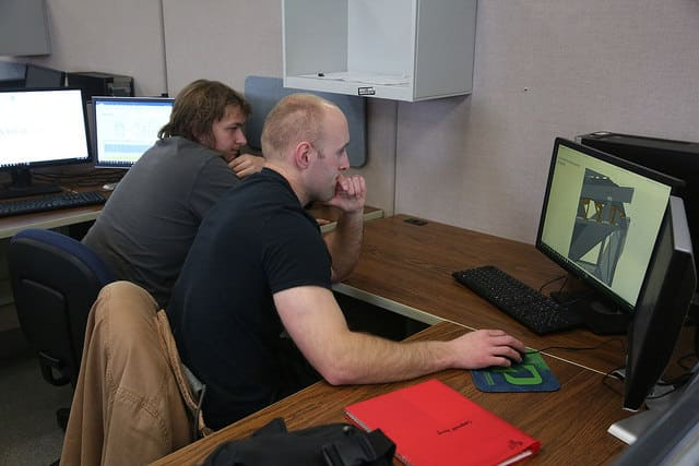 Two mechanical design students working on a computer together.