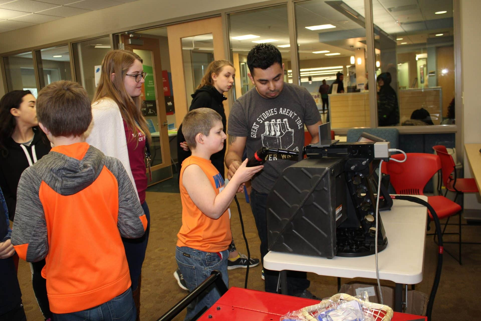 Nick Martinez teaches a kids about the virtual welder at Boys and Girls Club