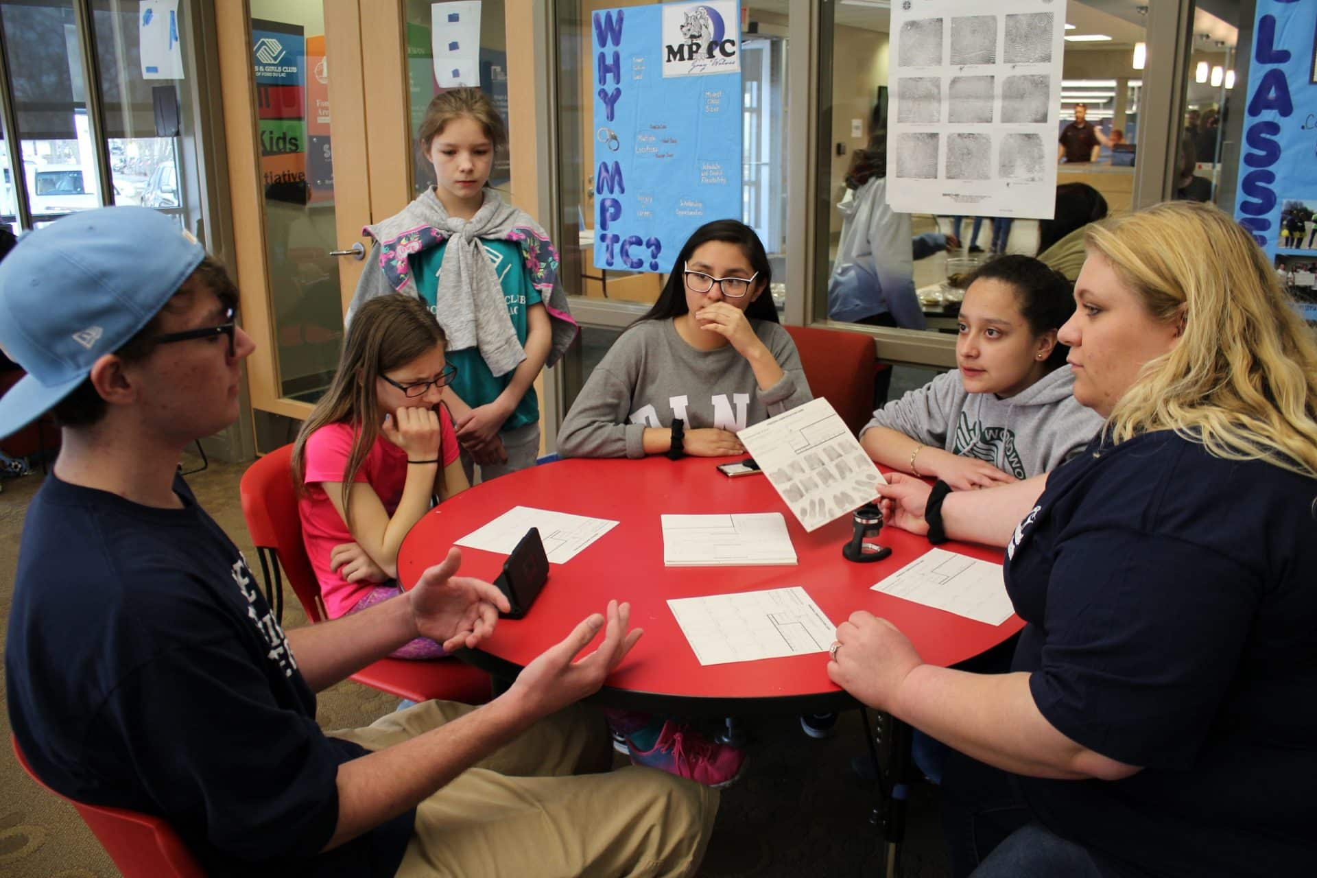 Boys and girls club students around a table talking.