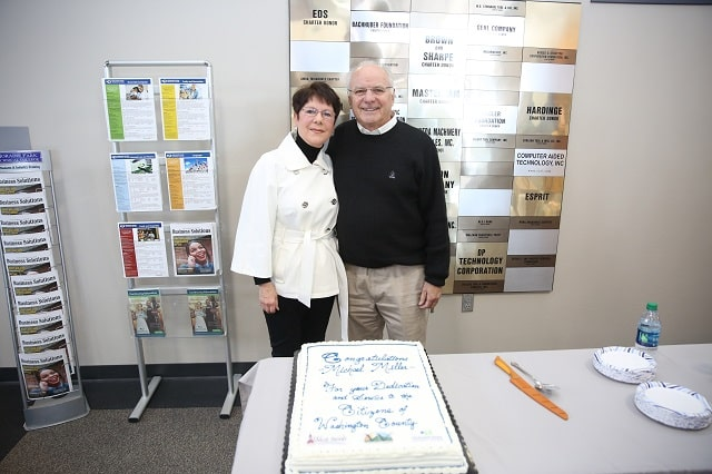 Mike Miller and his wife pose by his cake.