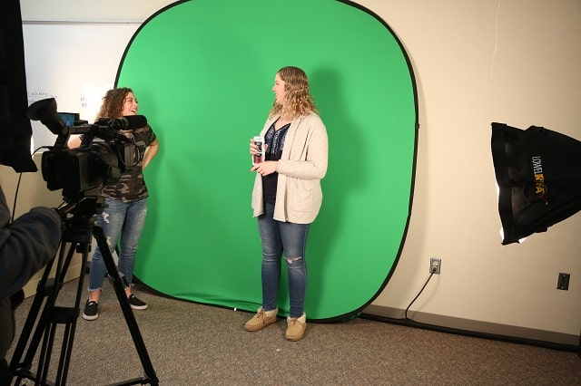 Marketing students working with a green screen to shoot a commercial.