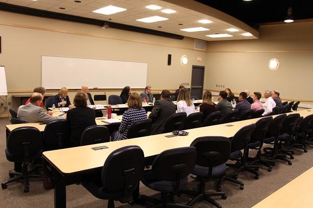 Students, staff and legislators seated at large table at legislative breakfast.