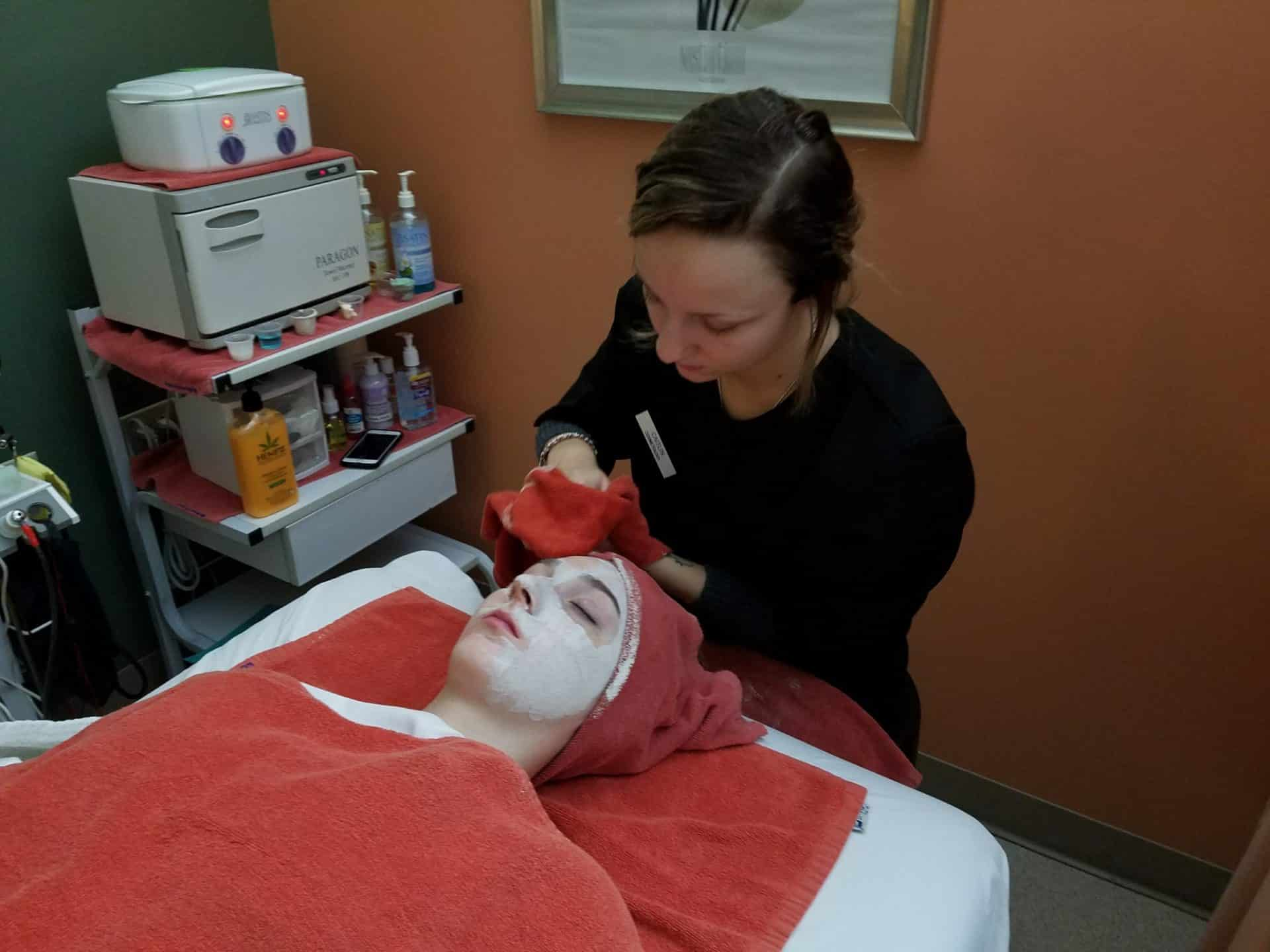 Cosmo student giving a client a facial service