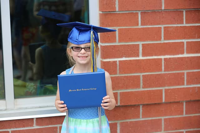 young girl trying on graduation cap