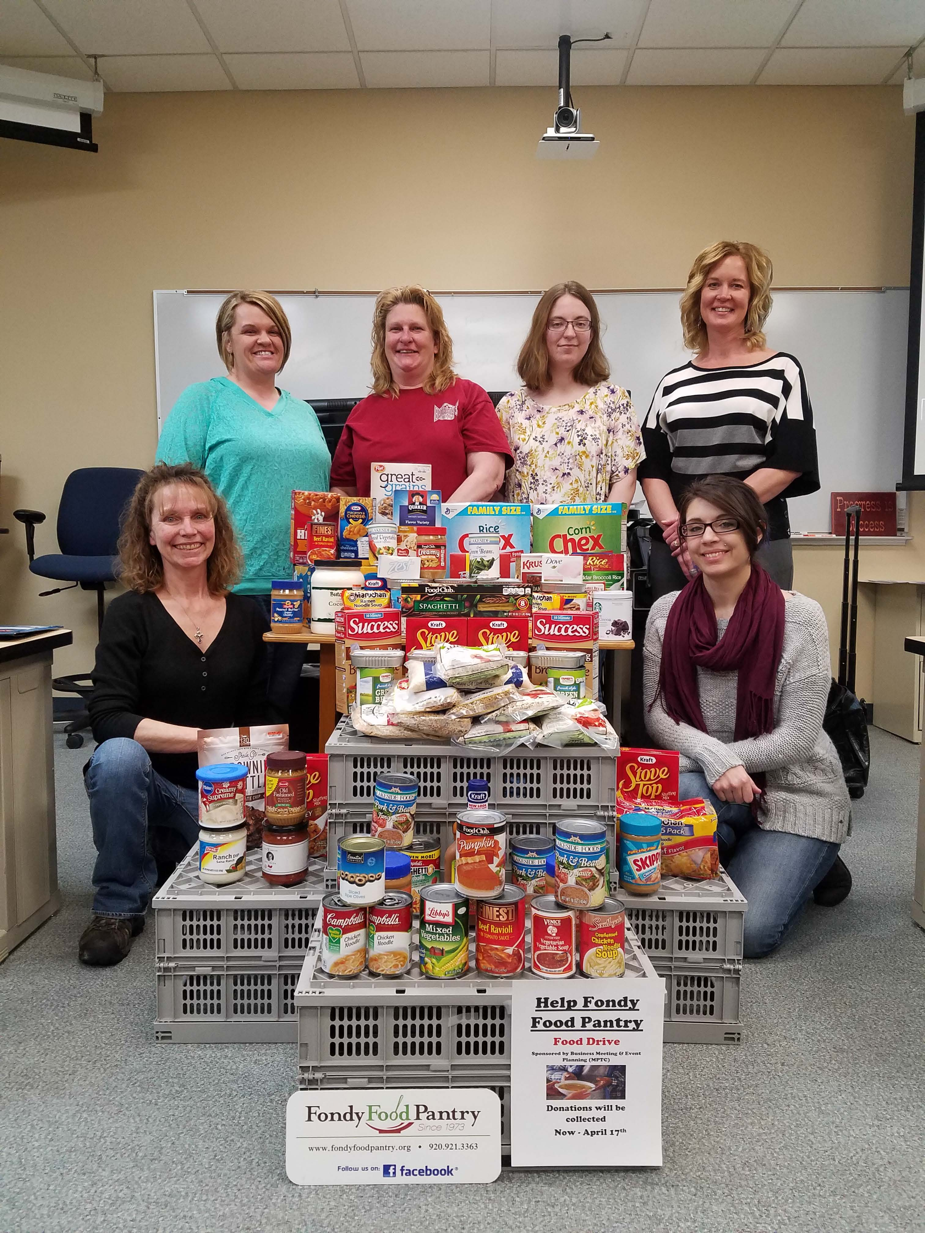 Students pose by boxed goods for food pantry donation