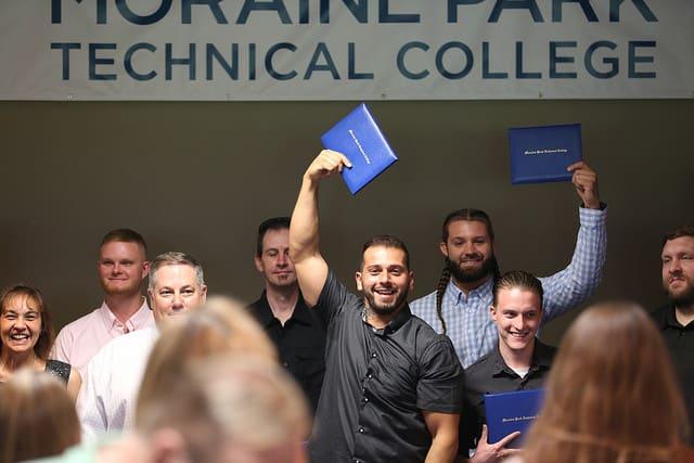 graduates show off their diploma