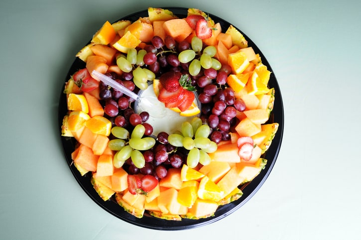 A delicious fresh fruit tray with dip.