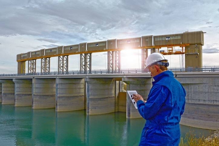 Engineer inspecting a hydroelectric dam. He uses a tablet device to record and communicate data.