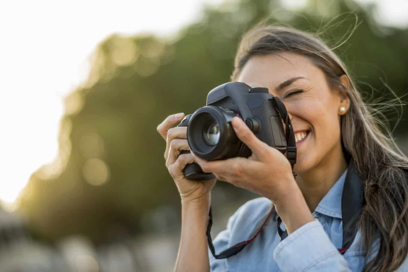 Female photographer taking pictures outdoors and holding a camera