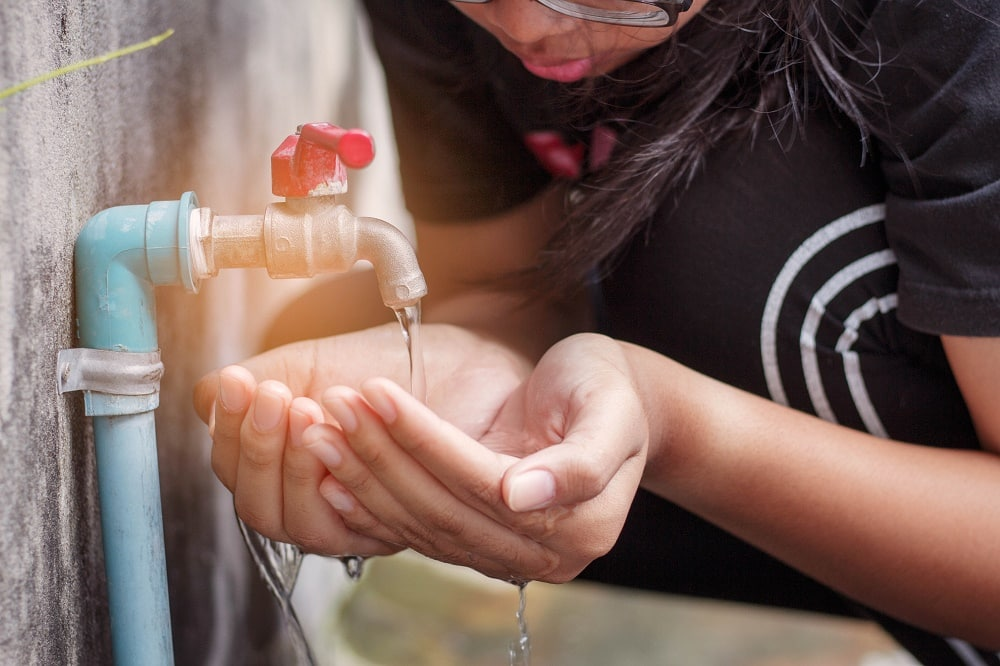 hands of a young woman watering the old water faucet.