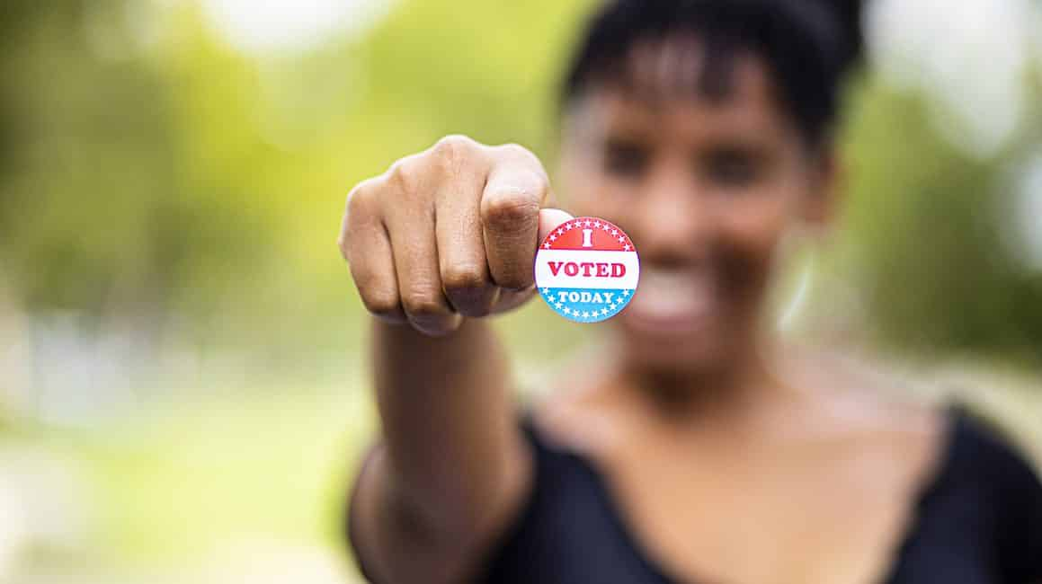 "woman holding ""i voted"" sticker"