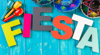 """colorful tabletop with sombreros, maracas and letters that spell out """"Fiesta"""""""