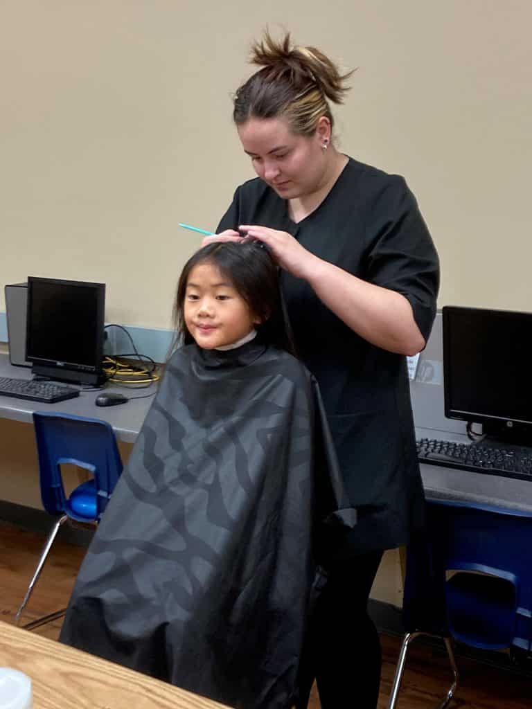 cosmetology students cut hair at boys and girls club